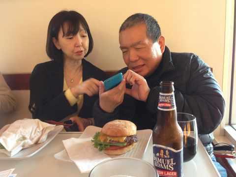 ハンバーガーを食べようとしている岩下さんと、内容を説明する藤井さんの写真