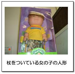 杖をついている女の子の人形